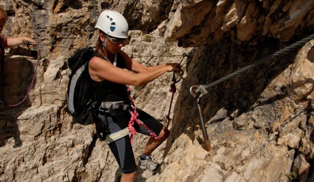 woman rock climbing in helmet