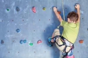 boy rock climbing indoors